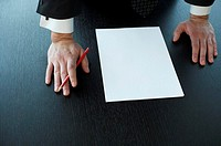 A white sheet of paper between businessman's hands