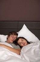 Young couple lying next to each other in bed sleeping