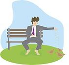 Businessman sitting on a bench and feeding birds