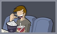 Boy eating popcorns in a movie theater