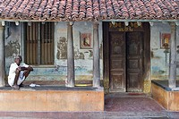 A man sitting on the porch of his typical Tamil House in Pondicherry. India