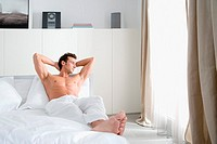 Man relaxing in bedroom (thumbnail)