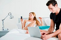 Couple on bed with laptop and handheld computer