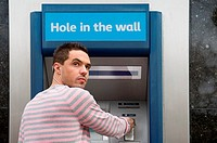 Man looking over shoulder at cash machine