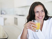 Woman in robe with glass of orange juice smiling (thumbnail)