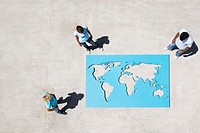 Aerial view of three people looking down at world map