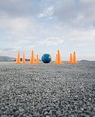 Globe on gravel outdoors surrounded by traffic cones