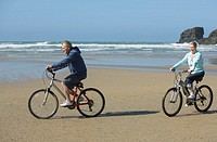 a couple riding bikes at the beach