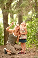 Young woman and child in woods looking at scenery, Regina, Saskatchewan