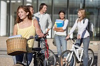 Young Woman on bicycle with students in background