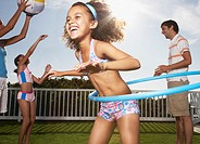 Girl in swimsuit with hula hoop and family playing in background