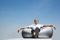 Businesswoman sitting on beanbag chair outdoors with eyes closed (thumbnail)