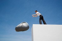 Businesswoman tossing beanbag chair off wall outdoors