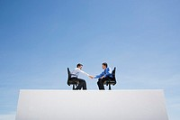 Two businessmen on wall with office chairs shaking hands