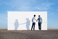 Two men shaking hands outdoors with wall