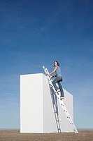 Woman climbing ladder on wall outdoors