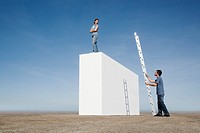 Woman standing on wall and man with ladder outdoors