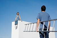Woman sitting on wall and man with ladder outdoors