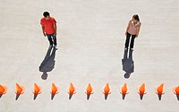 Man and woman looking at each other with row of traffic cones