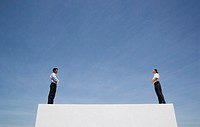 Businessman and woman standing outdoors on wall