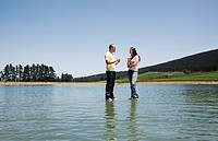 Man and woman standing on water talking