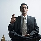 Businessman meditating near a Buddha statue