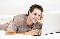 Man lying in bed using a laptop