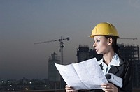 Businesswoman wearing a hardhat and holding a blueprint