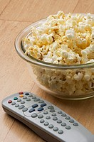 Close-up of a remote control and popcorn in a bowl