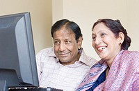 Close-up of a mature couple working on a computer and smiling