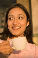 Close-up of a businesswoman holding a coffee cup and smiling