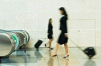 Blurred view of two businesswomen carrying their luggage