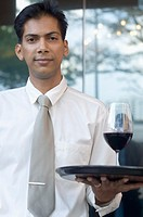 Portrait of a mid adult man holding a glass of red wine on a tray