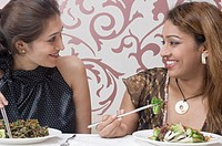 Close-up of two young women eating food with chopsticks