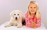girl beside kuvasz puppy
