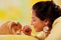 woman feeding guinea pig - Cavia spezies