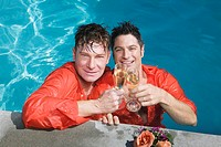 Fully clothed gay couple drinking champagne in swimming pool