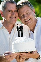 Gay couple displaying wedding cake with two grooms