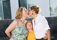 Lesbian couple kissing over their son
