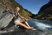 Woman dipping her feet in river in forest valley (thumbnail)