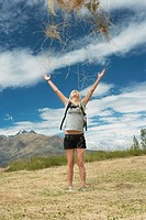 Female hiker throwing grass into air in field (thumbnail)