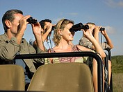 Group of tourists on safari sitting in jeep looking through binoculars close_up
