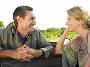 Man and woman talking woman leaning elbow on door of jeep smiling