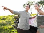 Couple on safari man pointing map on jeep