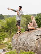 Man and woman on rock looking at view man pointing