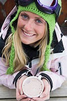 Young woman in ski-wear with cup of hot chocolate, close-up, high angle, portrait