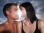 Couple about to kiss with sun behind outdoors