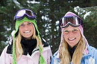 Portrait of two young blonde women wearing ski-wear in forest