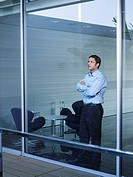 Young businessman standing at window in office, arms crossed
