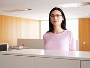 Young businesswoman standing in office, portrait